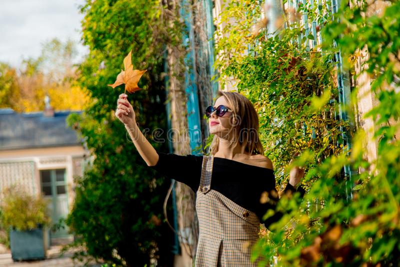 Young girl in sunglasses holding a leaf royalty free stock photo