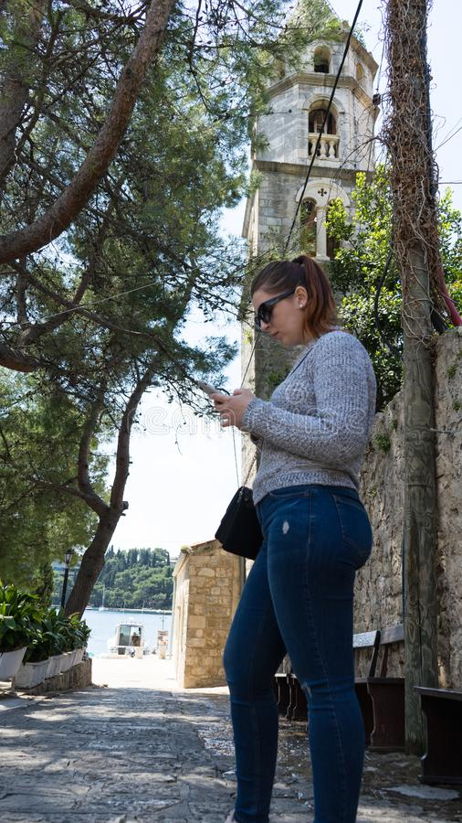 Young Girl with sunglasses sending a message in her smart phone. Red head woman standing in casual clothes in coastal town of stock photography