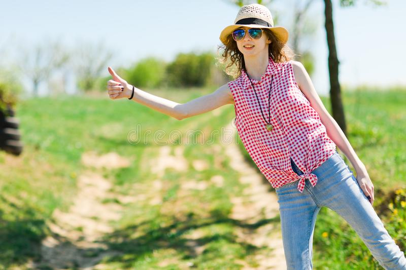 Young girl with sunhat hitchhiking on of road stock photos