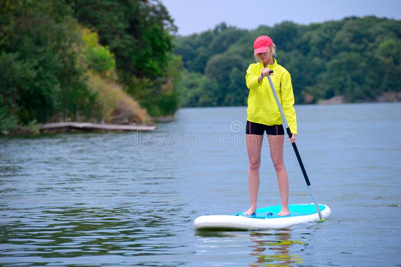 Young girl-surfer riding on the stand-up paddle board in the clear waters of the on the background of green trees stock photos