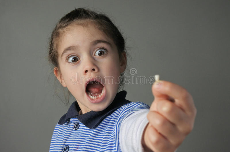 Young girl surprise to find that she have lost her first milk te stock image