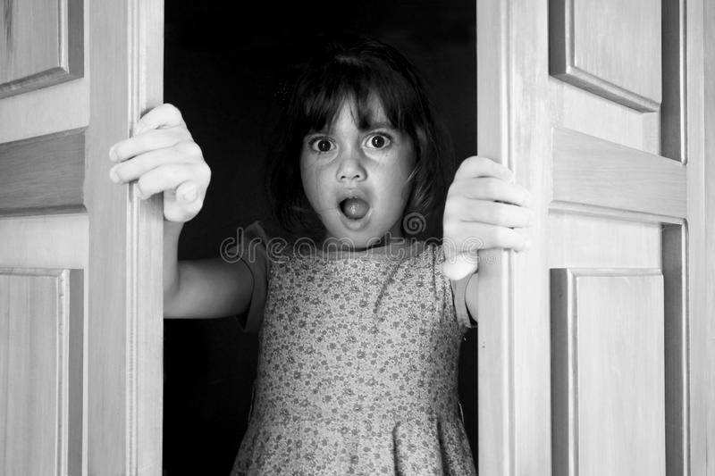 Young girl surprised to find and see what is behind closed doors royalty free stock image