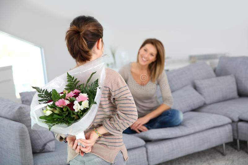 Young girl surprising her mother with flowers. Young girl giving flowers to her mom for birthday royalty free stock image