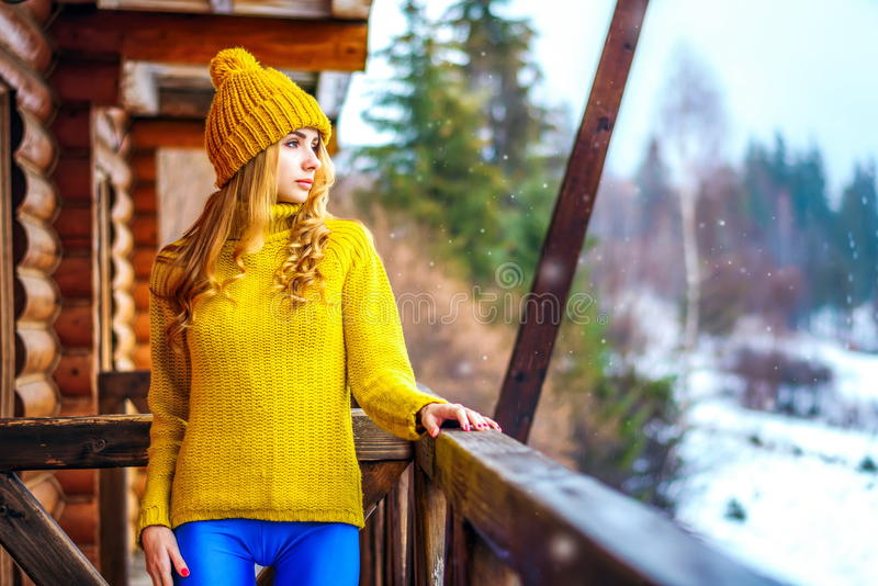 Young girl in a sweater standing on a wooden porch royalty free stock images