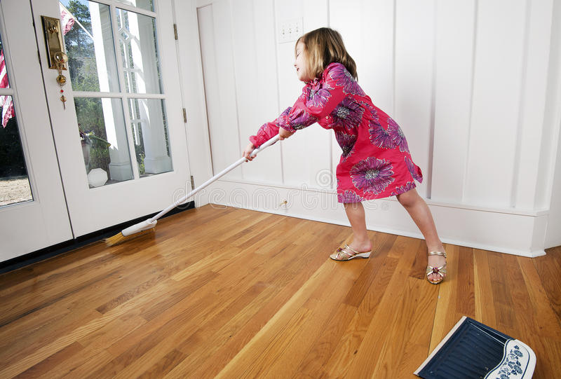 Young girl sweeping /cleaning stock images