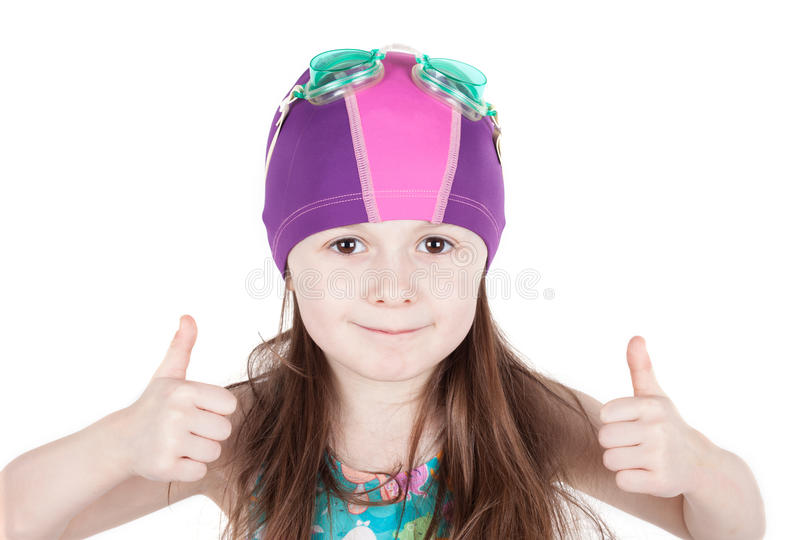 Young girl swimmer with OK gesture isolated on white background. Portrait of happy child girl in pool swimming cap isolated on white background. gesture of OK royalty free stock image