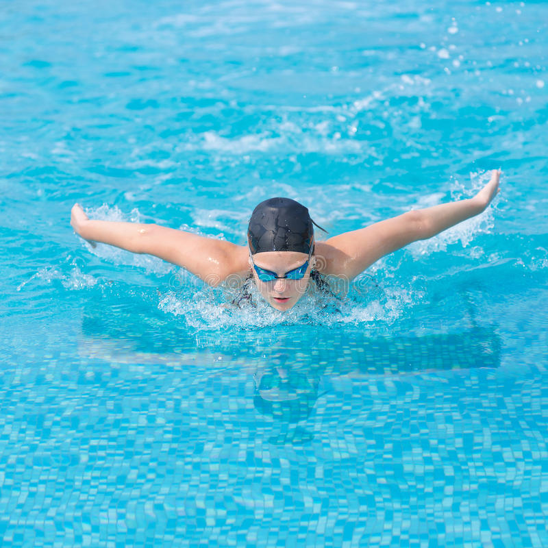 Young girl swimming butterfly stroke style royalty free stock images