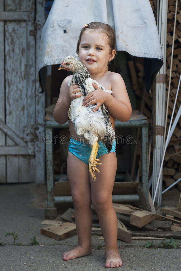 Young girl in swimsuit holding a chicken in her arms. royalty free stock photos