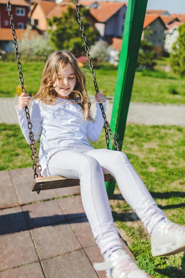 Young girl on swing at sunny day. royalty free stock photography