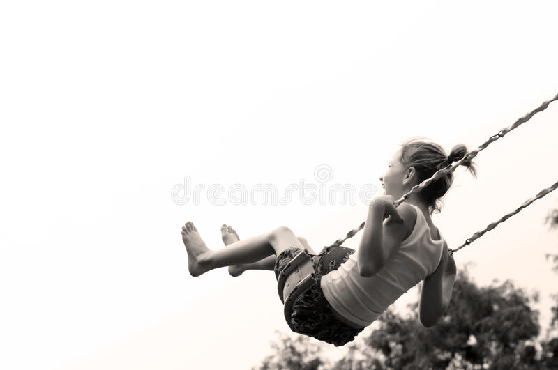 Young girl Swinging high royalty free stock image