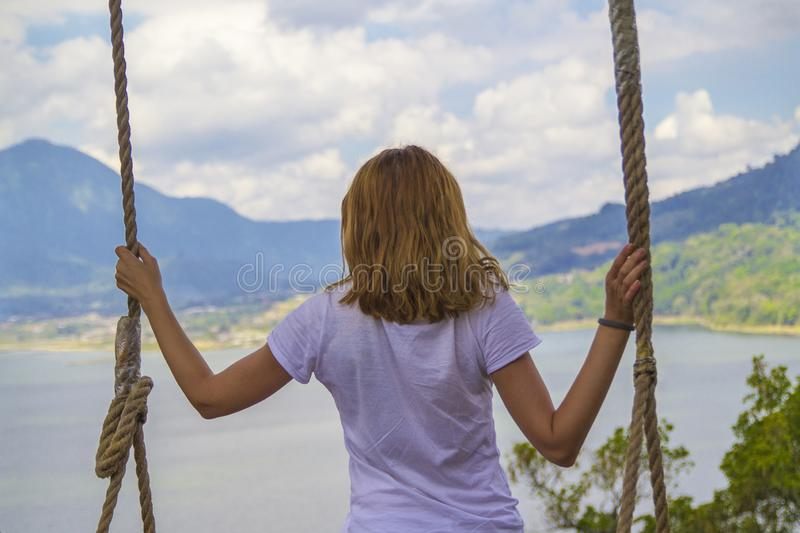 Young girl swinging overlooking a lake and mountains in nature. Back view, person, summer, woman, adventure, female, green, hanging, jungle, rope, dangerous stock images