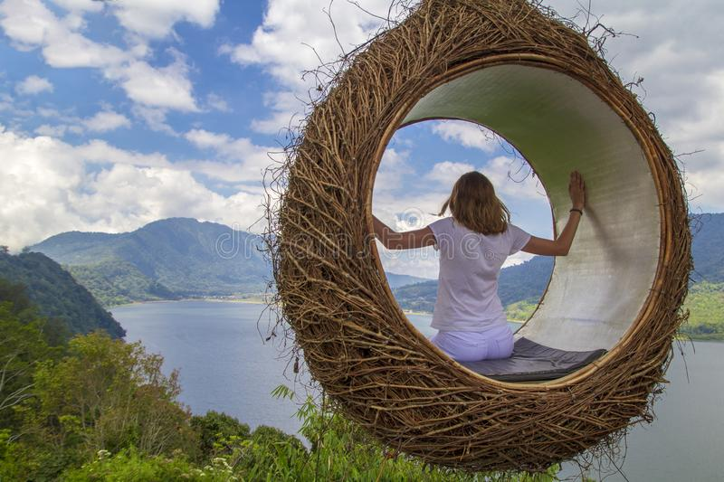 A young girl swinging on a swing in the form of a nest overlooking the lake and mountains in nature. Back view, person, summer, landscape, woman, adventure royalty free stock image
