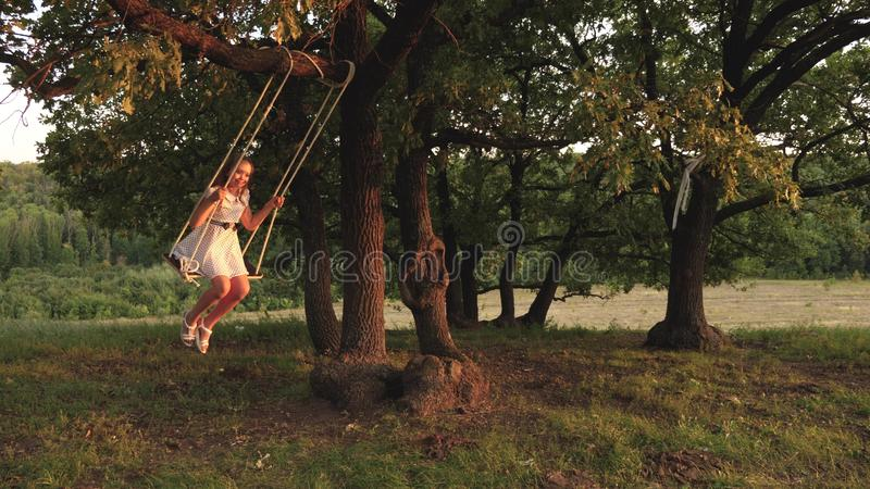 Young girl swinging on a swing under a tree in sun, playing with children. close-up. Family fun in nature. child rides a. Young girl swinging on a swing under a stock image