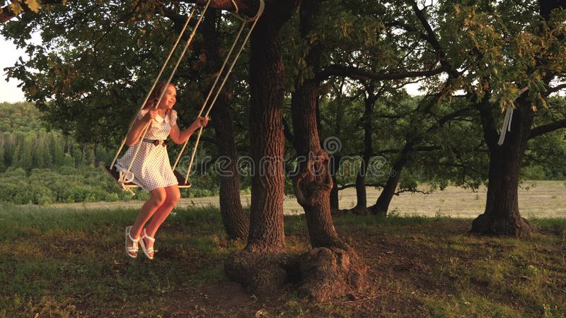 Young girl swinging on a swing under a tree in sun, playing with children. close-up. Family fun in nature. child rides a. Young girl swinging on a swing under a royalty free stock photography