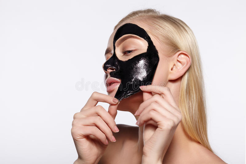 A young girl takes a black mask from her face. The gray background stock photo