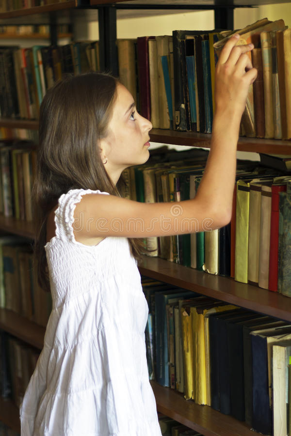 Download Young Girl Taking Book From Shelf In Old Library. Stock Image - Image of hair, indoors: 26158011