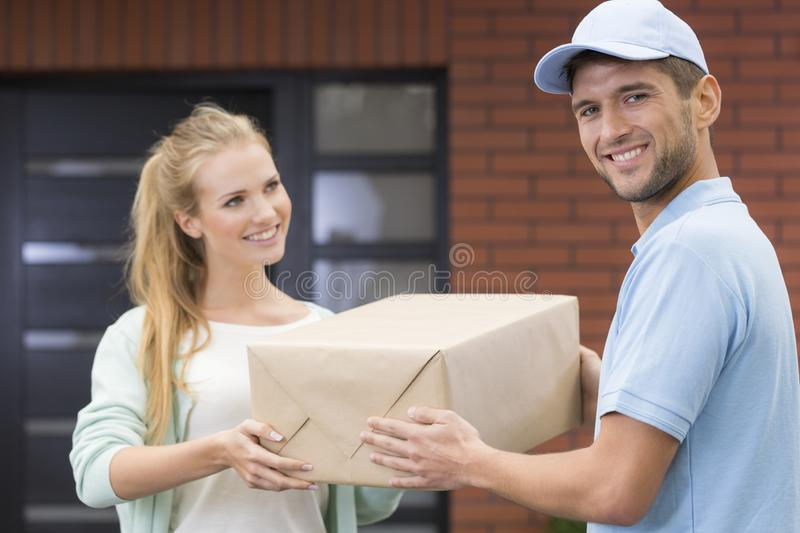 Girl taking a delivery form handsome courier in blue uniform. Young girl taking a delivery form handsome courier in blue uniform royalty free stock photos