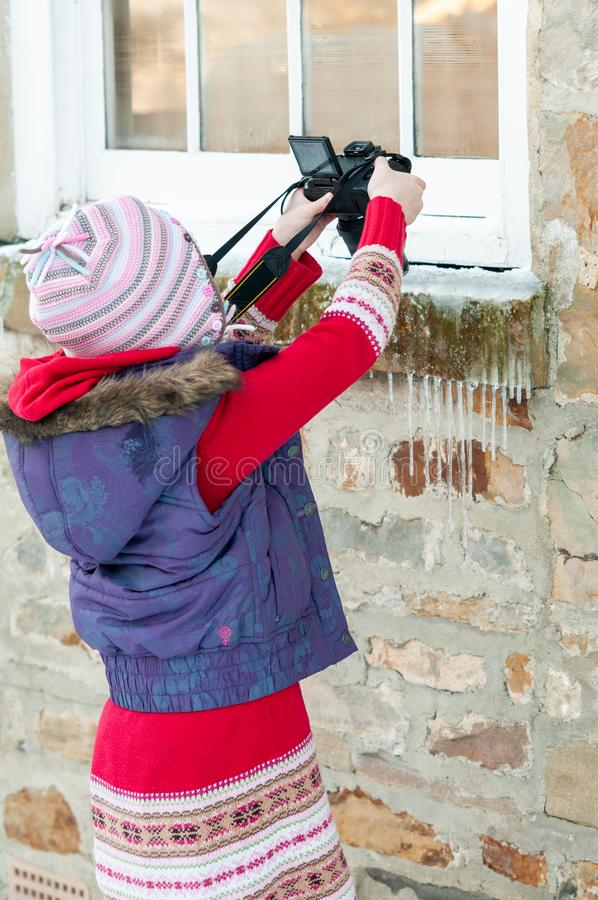 Young girl taking an overhead photograph of icicles hanging from a stone window ledge royalty free stock photos