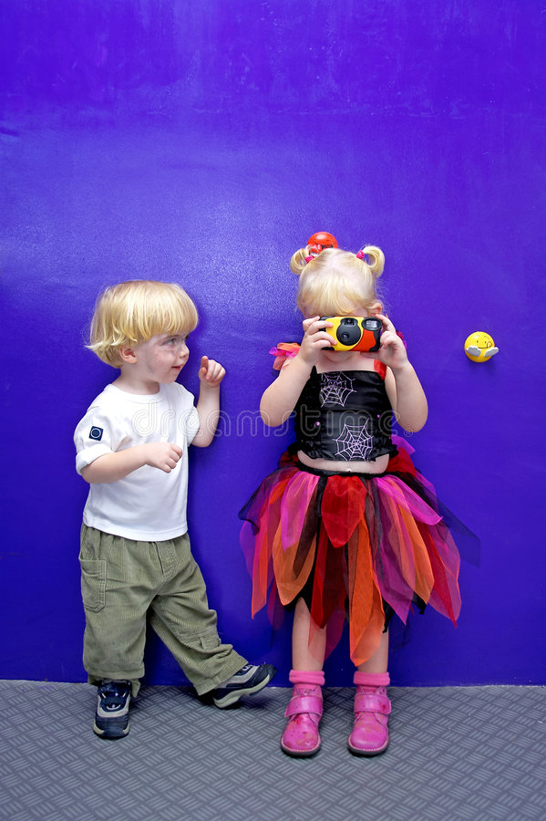 Young girl taking a photo with little boy watching royalty free stock image