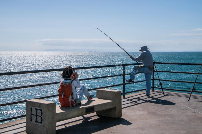 Young girl taking a picture of a fisherman fishing off of the end of the Huntington Beach Pier royalty free stock photos