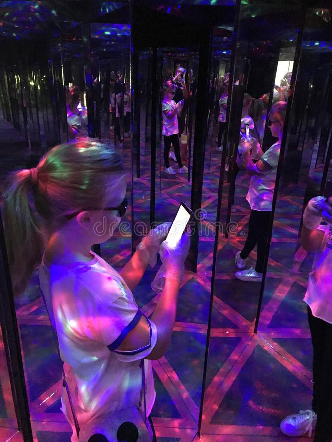 A young girl taking a selfie in hall of mirrors stock photos