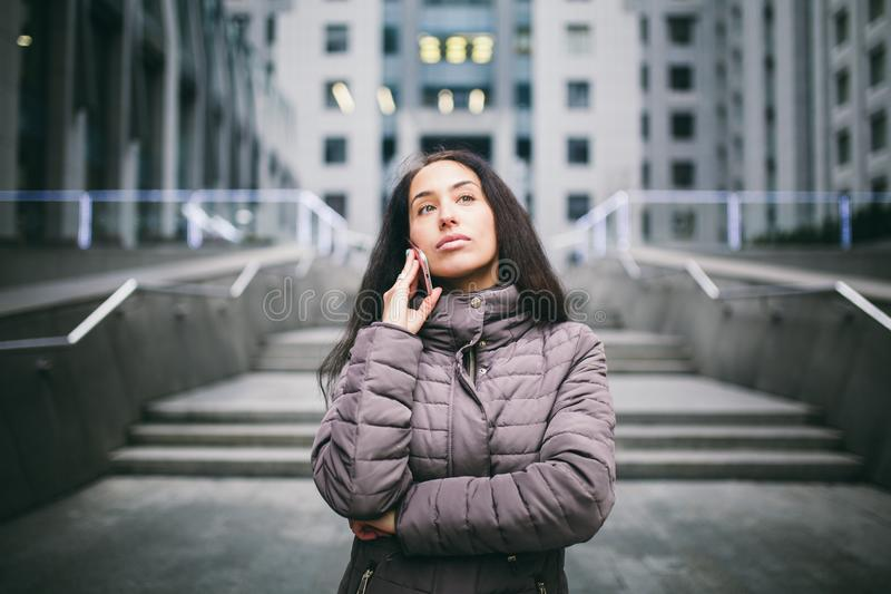 Young girl talking on mobile phone in courtyard business center. girl with long dark hair dressed in winter jacket in cold weather royalty free stock image