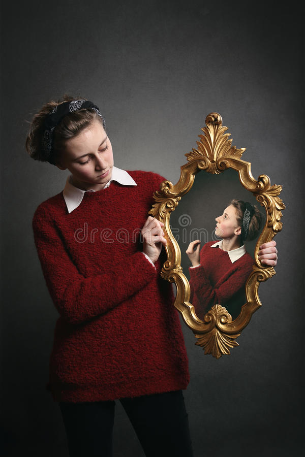 Young girl talks with her conscience. In a mirror stock photo