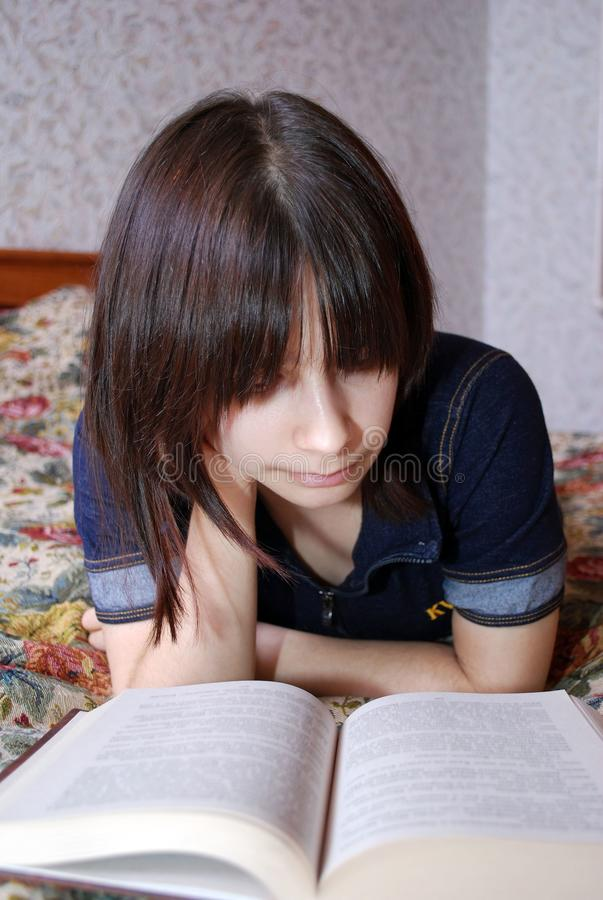 The young girl the teenager lies on a bed with the book. She was fond of reading. Education, self-development royalty free stock photos