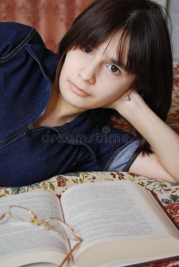The young girl the teenager lies on a bed with the book. She was fond of reading. Education, self-development royalty free stock photo