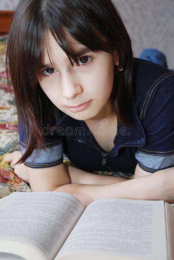 The young girl the teenager lies on a bed with the book. She was fond of reading. Education, self-development stock photos