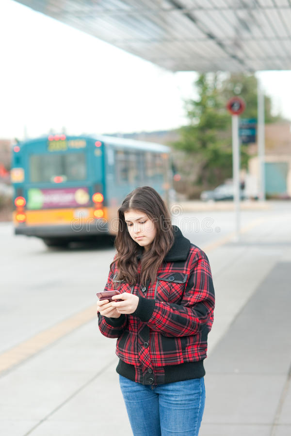 Young girl texting on bus stop stock image