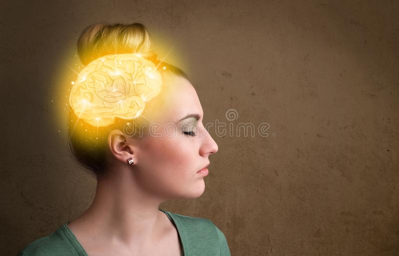 Young girl thinking with glowing brain illustration. On grungy background royalty free stock photography