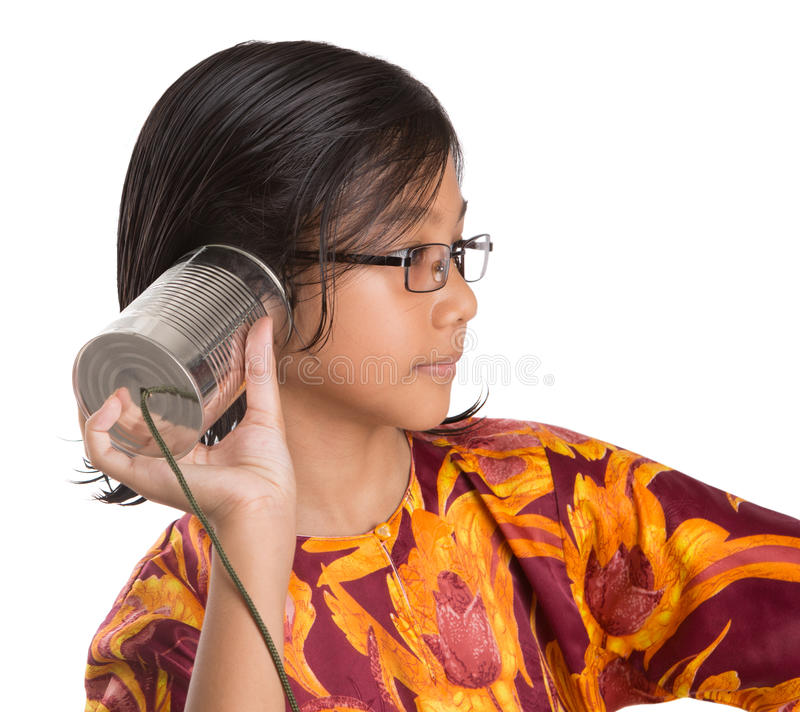Young Girl With Tin Can Telephone III. An Asian young girl with tin can telephone over white background stock photography