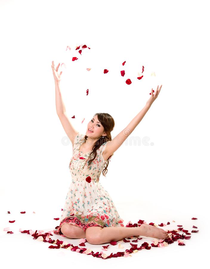 Young girl tossing rose petal stock image
