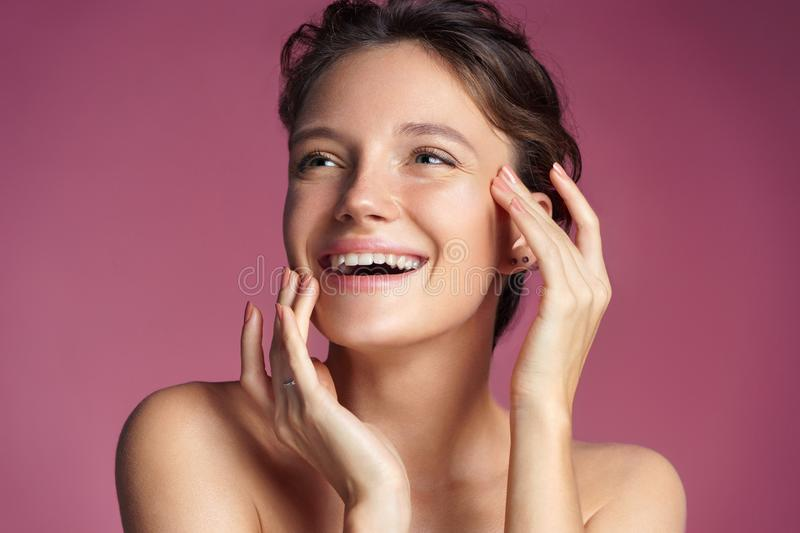 Young girl touching her healthy skin on pink background. royalty free stock photography