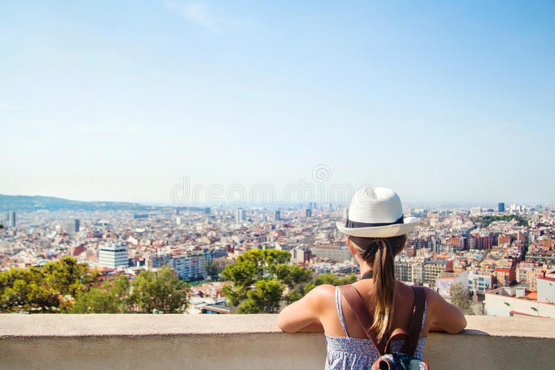 Young girl tourist with a backpack looking at the city Barcelona. Young girl tourist with a backpack looking at a panoramic view of the city Barcelona, Spain royalty free stock images