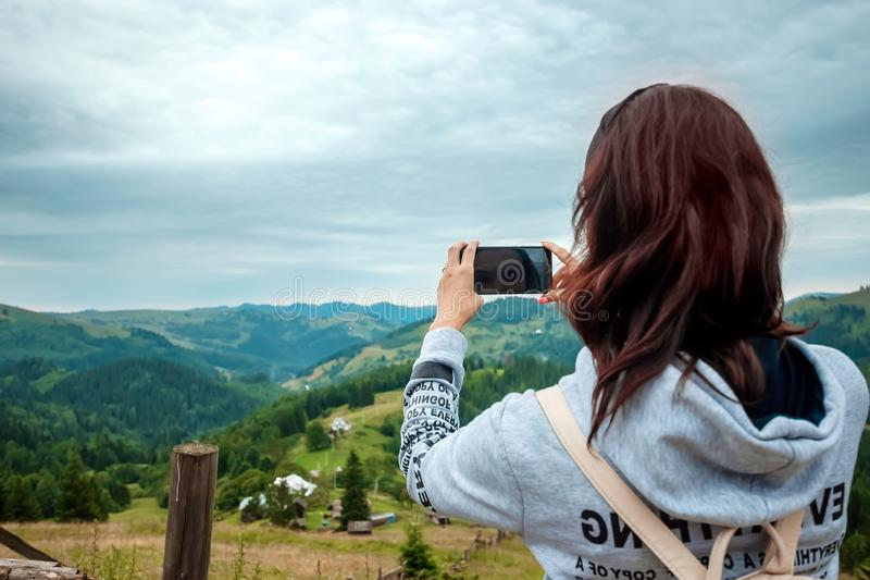 A young girl tourist with a backpack standing on top of a mountain photographs on a telephone a mountain landscape. The concept of royalty free stock photography