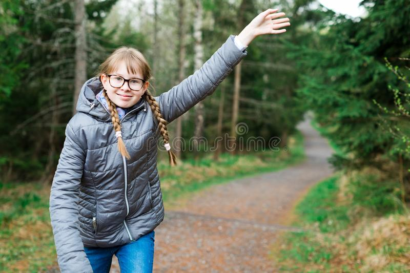 Young girl tourist in gray jacket on walking trail in th forrest stock photo
