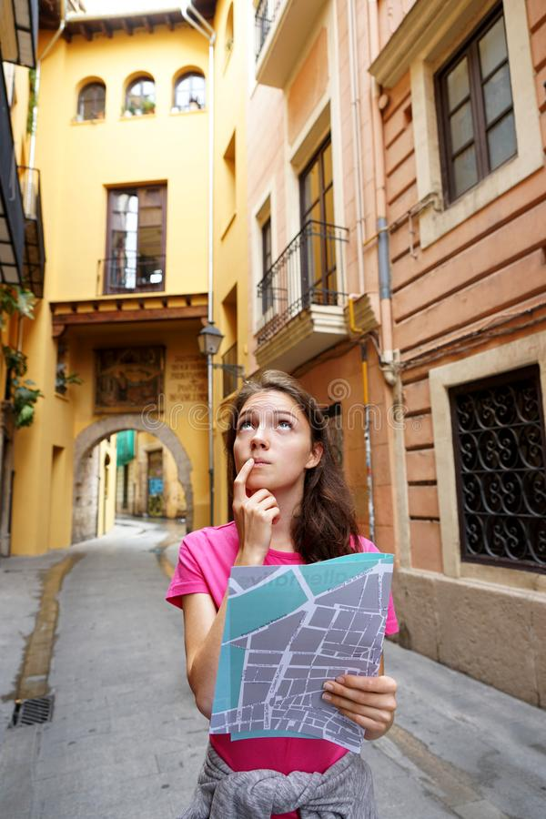 Young girl tourist with map searching for directions on the street. stock photo