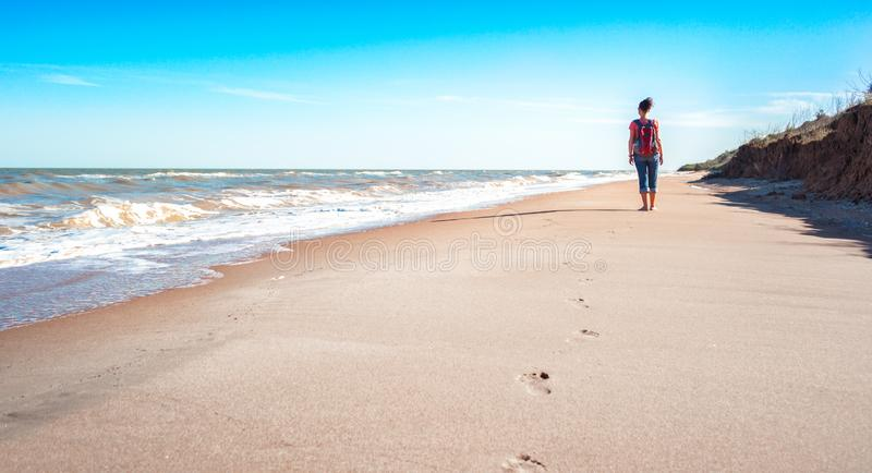 Young girl tourist with a red backpack on an empty sandy beach near the surf of the sea on a background of blue sky and clouds in royalty free stock photography