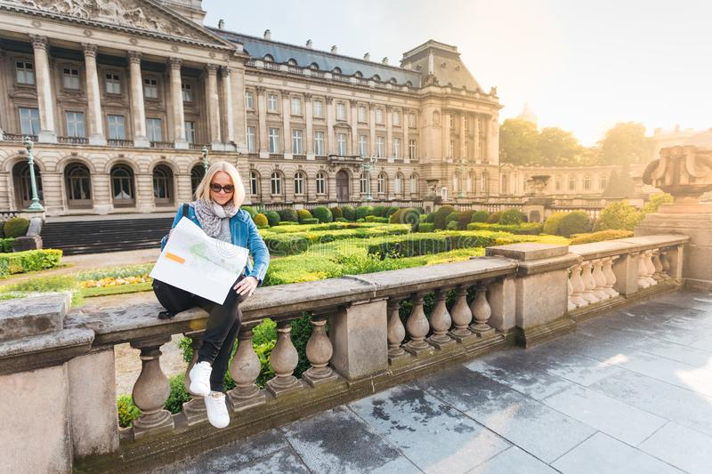 Young girl tourist sits on the background of the Royal Palace in Brussels and looks into the city map, Belgium royalty free stock photography