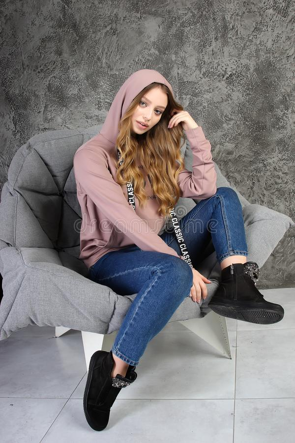 Young girl in a tracksuit sits in  a stylish interior. royalty free stock image