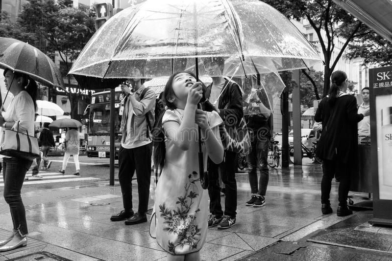A Young Girl Holding an Umbrella in the Rain stock photos