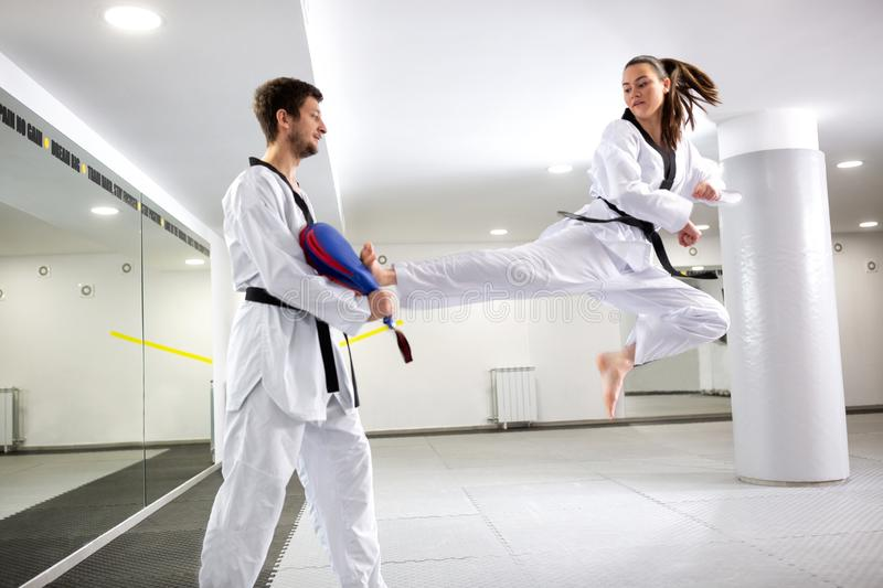 Young girl training martial art of taekwondo performing a kick from a jumping position. Physical performance royalty free stock photos