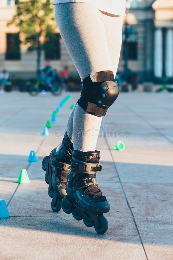 Young girl training the riding on roller skates. Closeup of female legs with roller skates. And protectors royalty free stock photography