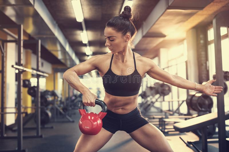 Girl on training with kettle bell weight in fitness center stock photography
