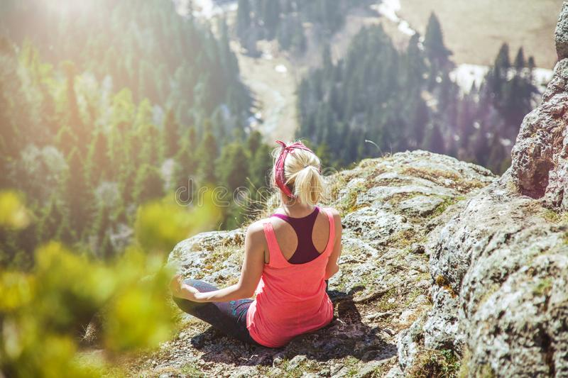 Young girl traveler sits on top of a mountain in a yoga pose. The girl loves to travel. Concept for travelers. View from royalty free stock photo