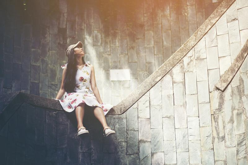 Young girl traveler sitting on circle stairs of a spiral staircase of an underground crossing in tunnel at Fort Canning Park, Sin stock photo