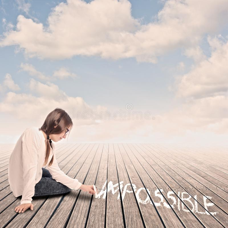 Young girl turning the word impossible to possible stock photo