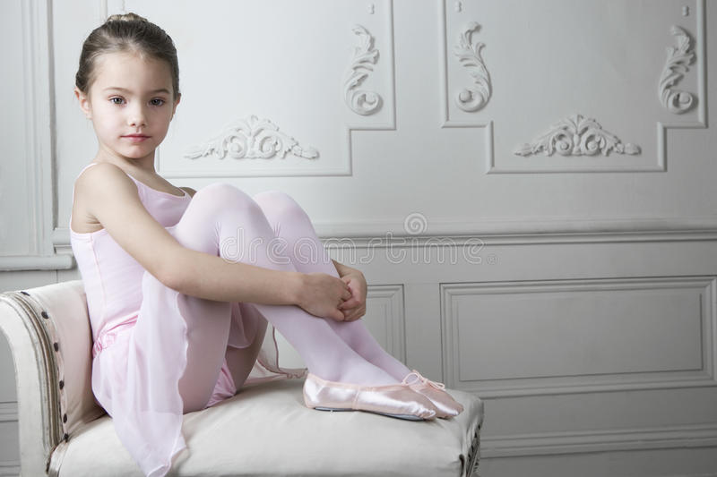 Young girl in a tutu and ballet shoes sitting on a chair stock photo